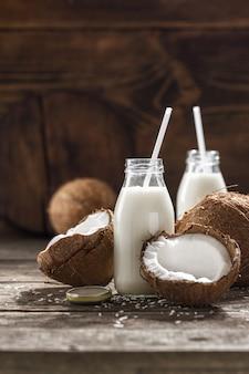 Lait de coco en bouteilles sur table en bois. concept d'alimentation saine