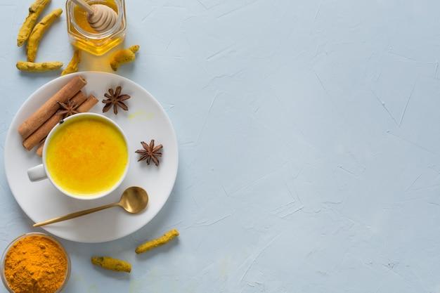 Lait de curcuma doré avec du miel et des ingrédients sur bleu.