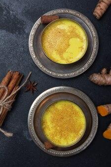 Lait de curcuma doré sur fond noir avec ingrédients