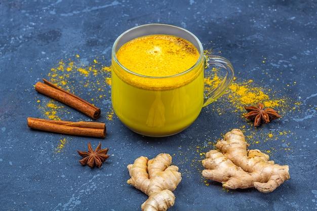 Lait de curcuma indien traditionnel dans une tasse en verre avec étoile d'anis, gingembre et cannelle