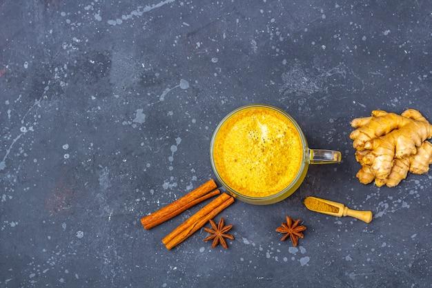 Le lait de curcuma indien traditionnel est du lait doré dans une tasse en verre avec du curcuma et du gingembre racine, de la cannelle, de l'étoile d'anis sur fond sombre. perte de poids, boisson saine et bio. fermer