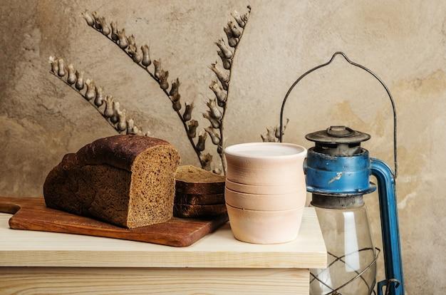 Lait dans un pot en céramique et pain de seigle. nature morte au style rustique