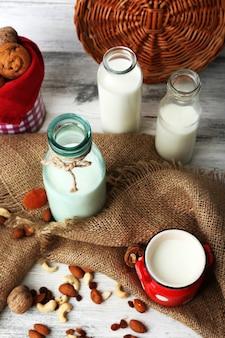 Le lait dans la verrerie et les noix sur la table en bois avec un sac, gros plan