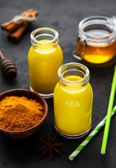 Lait doré avec cannelle, curcuma, gingembre et miel sur une surface de béton noir
