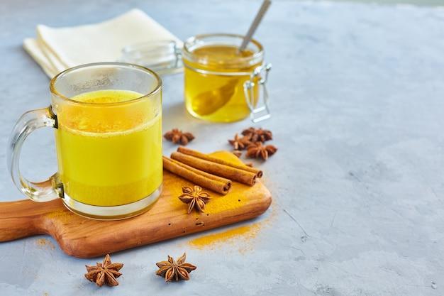 Lait doré chaud avec de la poudre de curcuma dans des verres