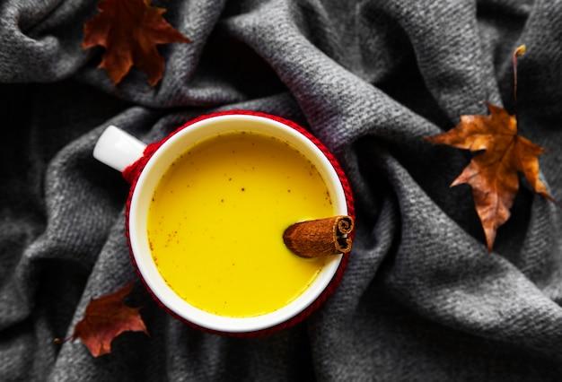 Lait doré dans une tasse blanche. feuilles d'automne. une boisson saine à base de lait, de curcuma, de cannelle et de miel.