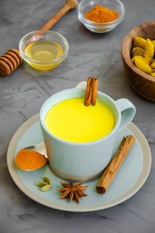 Lait doré dans une tasse avec du miel et d'autres épices
