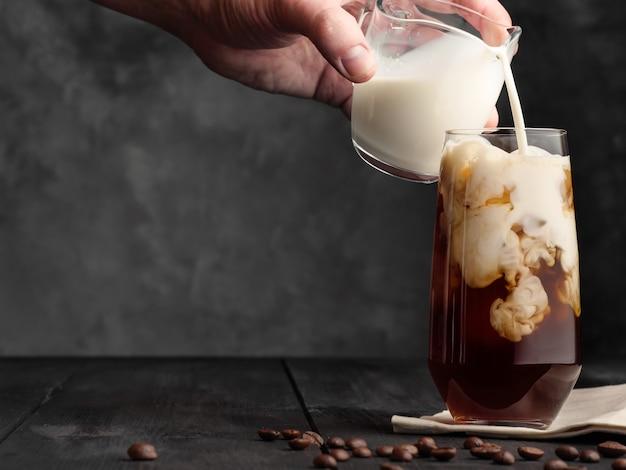 Le lait est versé dans un verre à whisky avec de la glace et du café sur une table en bois gris à partir d'un pot à lait. café au lait et glace.