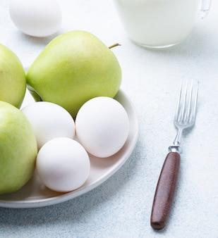 Lait, farine, œufs et pommes vertes sur fond blanc. ingrédients pour charlotte aux pommes. recette