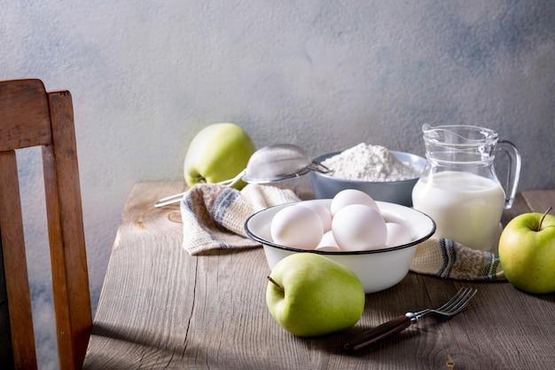 Lait, farine, œufs et pommes vertes sur une table en bois. ingrédients pour charlotte aux pommes
