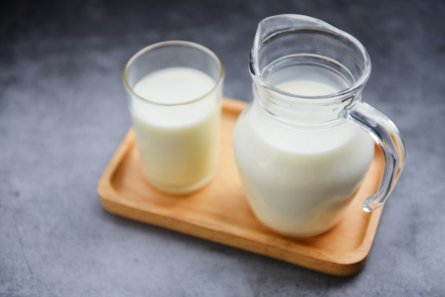 Lait frais naturel dans une cruche en verre sur un plateau en bois - servir le concept de lait pour le petit déjeuner