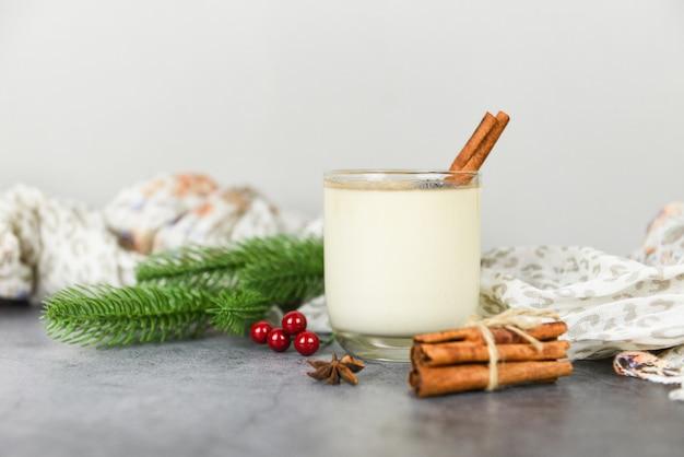 Lait de lait de poule délicieux boissons comme des soirées à thème avec pomme de pin à la cannelle et boule rouge pour noël traditionnel et vacances d'hiver