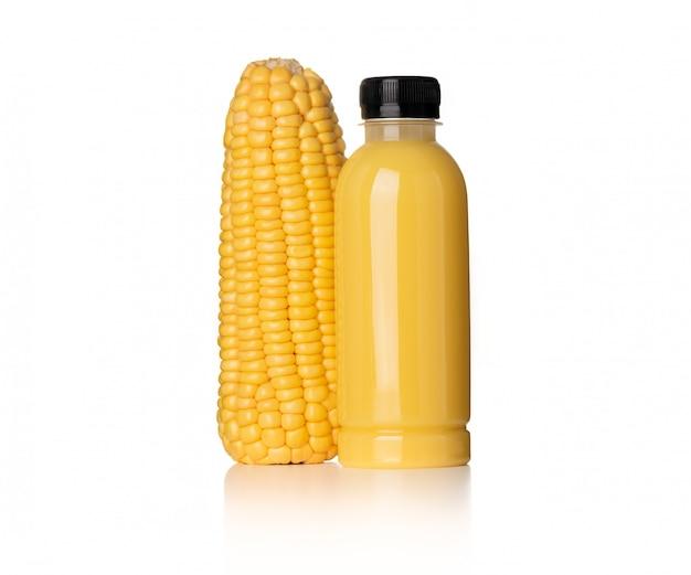 Lait de maïs en bouteille en plastique avec du maïs sur fond blanc
