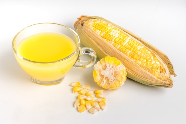 Lait de maïs et maïs sucré frais sur fond blanc