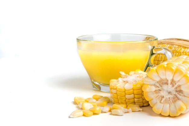 Lait de maïs et maïs sucré frais sur fond blanc.