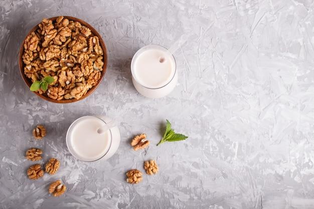 Lait de noix bio non laitier en verre et plaque de bois aux noix sur un béton gris.