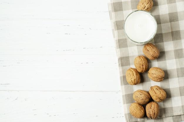 Lait de noix et de noix sur un torchon à carreaux sur fond de bois blanc.