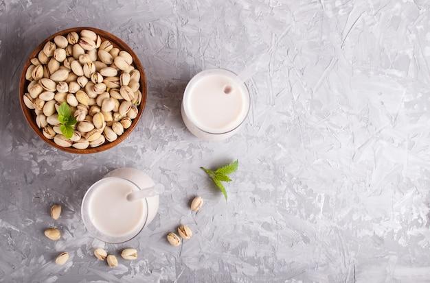 Lait de pistache biologique non laitier en verre et assiette en bois avec pistaches sur un béton gris.
