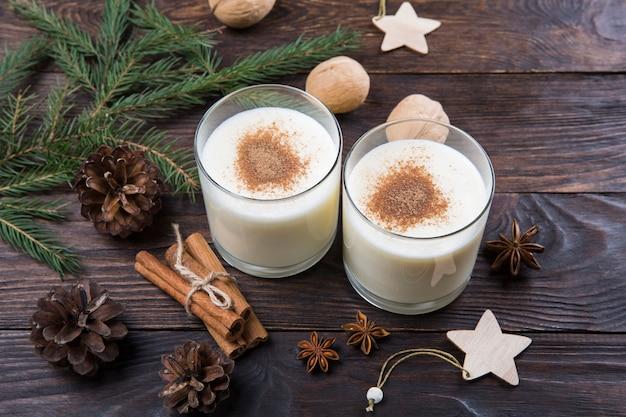 Lait de poule à la cannelle dans des verres, décoration de noël, boisson festive traditionnelle.