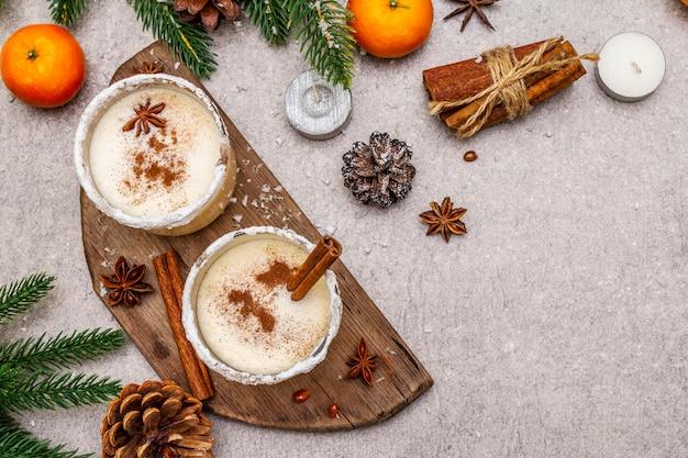 Lait de poule à la cannelle et à la muscade pour les vacances de noël et d'hiver. boisson maison dans des verres à bord épicé. mandarines, bougies, cadeau.