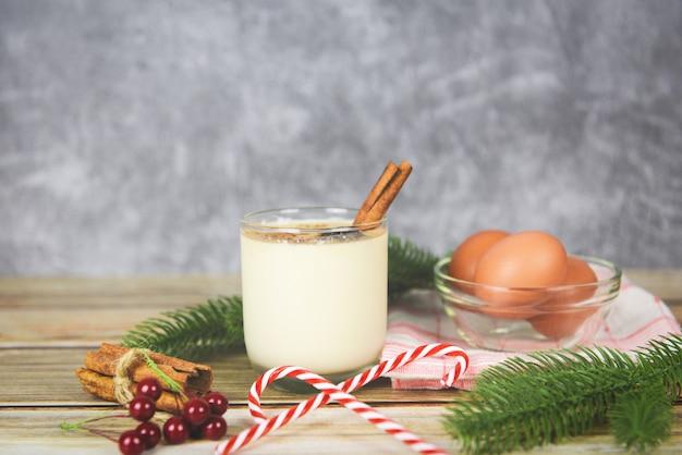 Lait de poule délicieuses boissons de vacances comme des fêtes à thème avec de la cannelle et de la muscade pour les fêtes traditionnelles de noël et d'hiver lait de poule fait maison dans des verres et des œufs frais décorés