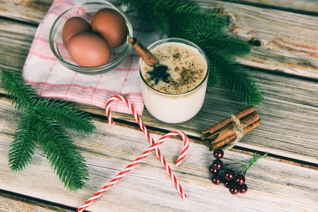 Lait de poule délicieuses boissons de vacances comme des fêtes à thème avec de la cannelle et de la muscade pour les fêtes traditionnelles de noël et d'hiver lait de poule fait maison dans des verres