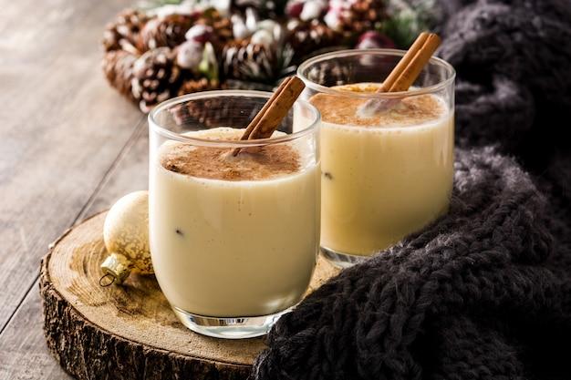 Lait de poule fait maison à la cannelle dans un verre sur la table en bois dessert typique de noël