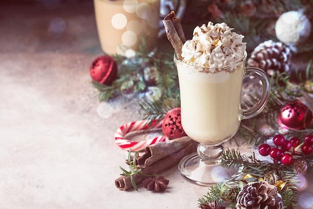 Lait de poule d'hiver traditionnel dans une tasse en verre avec du rhum au lait et de la cannelle recouvert de décorations de noël à la crème fouettée