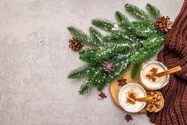 Lait de poule maison à la cannelle en verre. dessert de noël typique. brunch de sapin à feuilles persistantes, cônes, plaid confortable, neige artificielle.