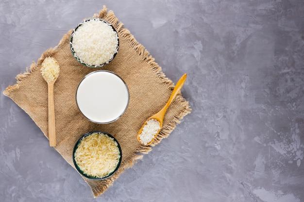Lait de riz et graines de riz sur fond gris