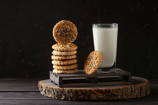 Lait sain frais et biscuits faits maison sur une table en bois foncé