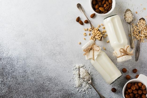 Lait végétal diététique fait maison et amandes, frisé, noisettes, flocons d'avoine, riz et noix de coco sur fond gris. concept de régime alimentaire sain.