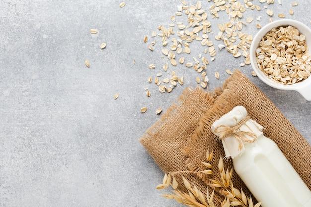 Lait végétal diététique fait maison à base de flocons d'avoine sur fond gris. concept de régime alimentaire sain. copiez l'espace et la bannière.