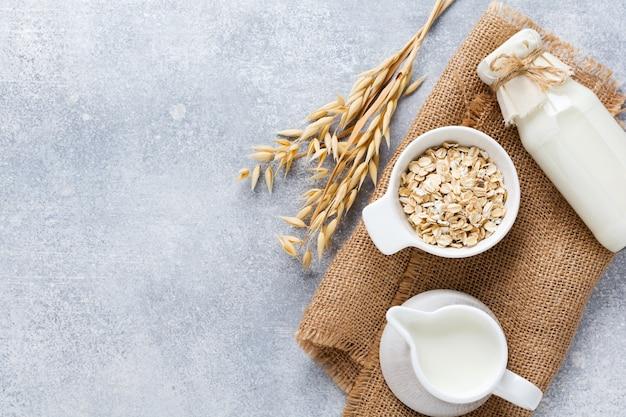 Lait végétal de régime fait maison à base de farine d'avoine sur fond gris. concept sain de régime. copiez l'espace et la bannière. vue de dessus.