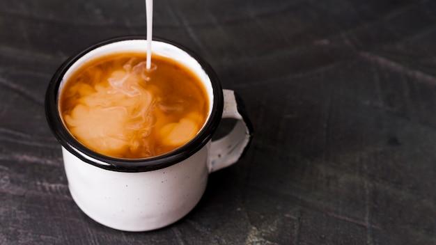 Le lait versé dans le café noir