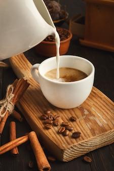 Lait versé dans l'espresso, gros plan. faire un fond de café, une tasse blanche et de la cannelle sur une vieille planche de bois rustique, espace pour copie
