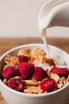 Le lait versé sur le musli et les framboises séchées