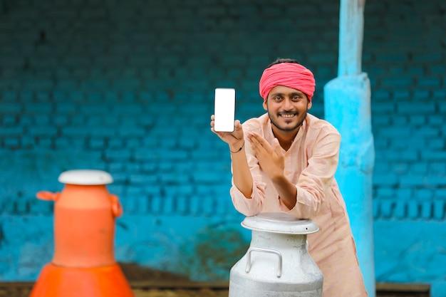 Laitier indien montrant l'écran du smartphone à la ferme laitière.