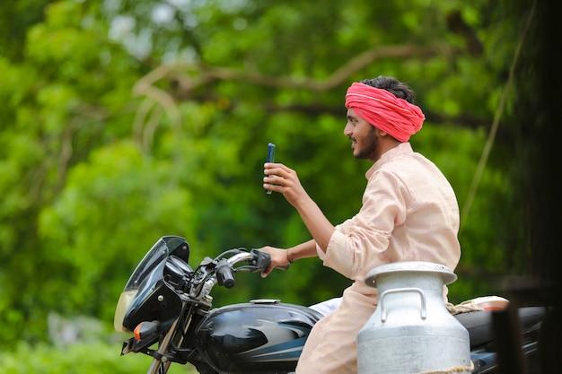 Laitier indien montrant l'écran du smartphone.