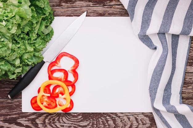 Laitue verte fraîche et poivrons sur du papier blanc avec une serviette en bande sur une table en bois