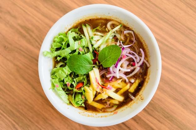 Laksa est une soupe de nouilles épicée sur une table en bois.