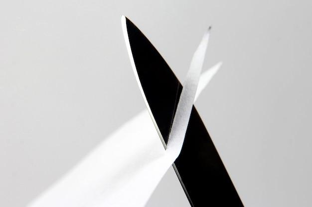 La lame d'un couteau tranchant a coupé le papier blanc. le tranchant de l'outil