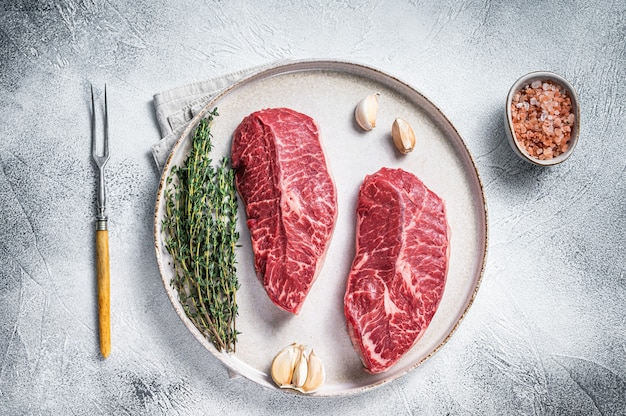 Lame de dessus d'huître crue ou steaks de viande de bœuf rôti de fer plat sur une assiette avec des herbes. vue de dessus.