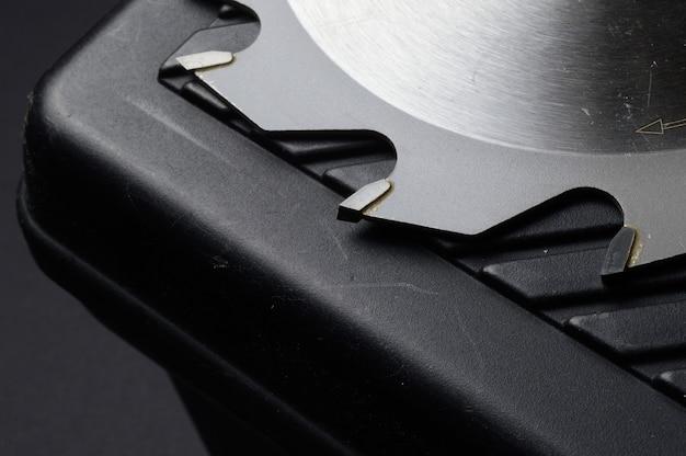 La lame de scie circulaire repose sur la boîte à outils. fermer.
