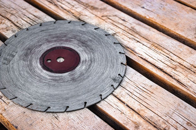 Une lame de scie circulaire repose sur une surface de planche de bois. ancienne lame diamantée pour couper le béton et la pierre. mise au point sélective douce.