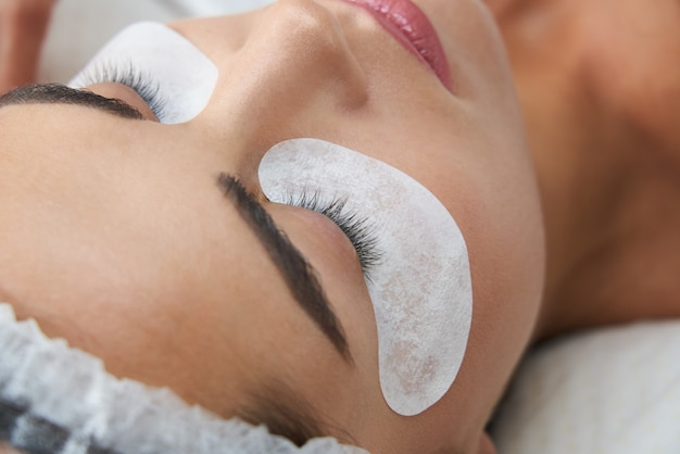 Laminage des cils et peinture en gros plan sur les procédures de beauté du visage dans une clinique de cosmétologie