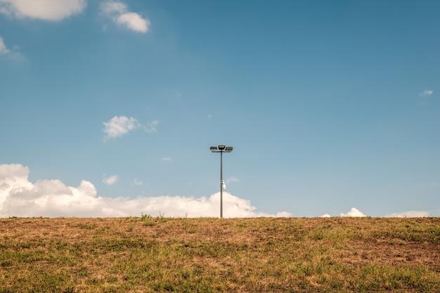 Lampadaire au milieu d'un champ contre un ciel bleu