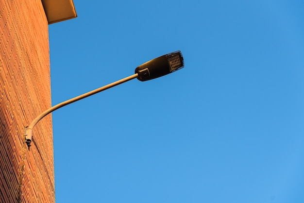 Lampadaire sur le mur rouge d'un immeuble avec un fond de ciel bleu