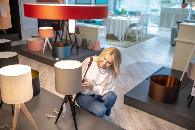 Lampadaire d'origine. belle femme accroupie près d'un lampadaire beige, le regardant, d'une humeur délicieuse