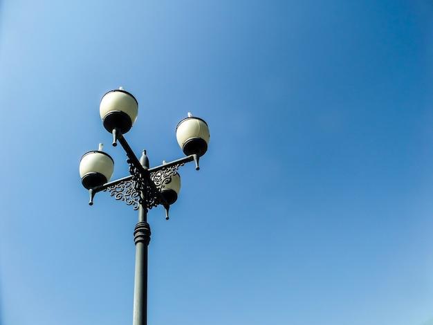 Lampadaire avec quatre lampes et fond de ciel bleu